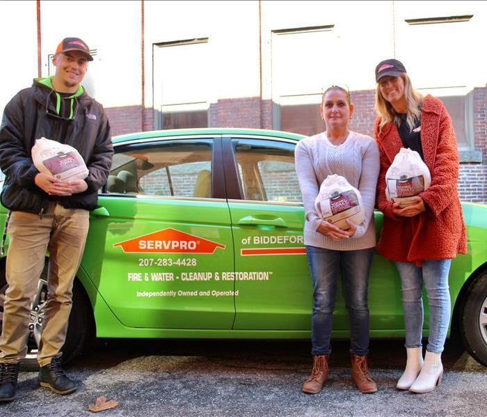 Chandler, Michelle & Kimberly holding some of the donated turkeys in front of a Servpro vehicle